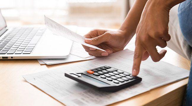 Mão fazendo conta na calculadora e faturas em cima da mesa